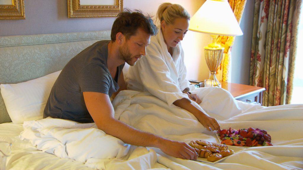 Oliver und Carolin haben die Nacht zusammen im Hotelzimmer verbracht und genießen ein gemeinsames Frühstück im Bett.