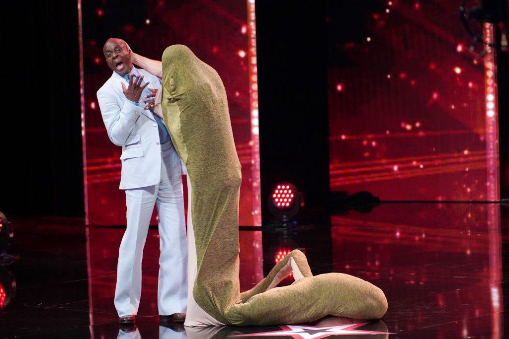 """Sethward Allison aus Amerika präsentiert eine Comedy-Schlangenperformance. Hier """"verschlingt"""" er Jurymitglied Bruce Darnell."""