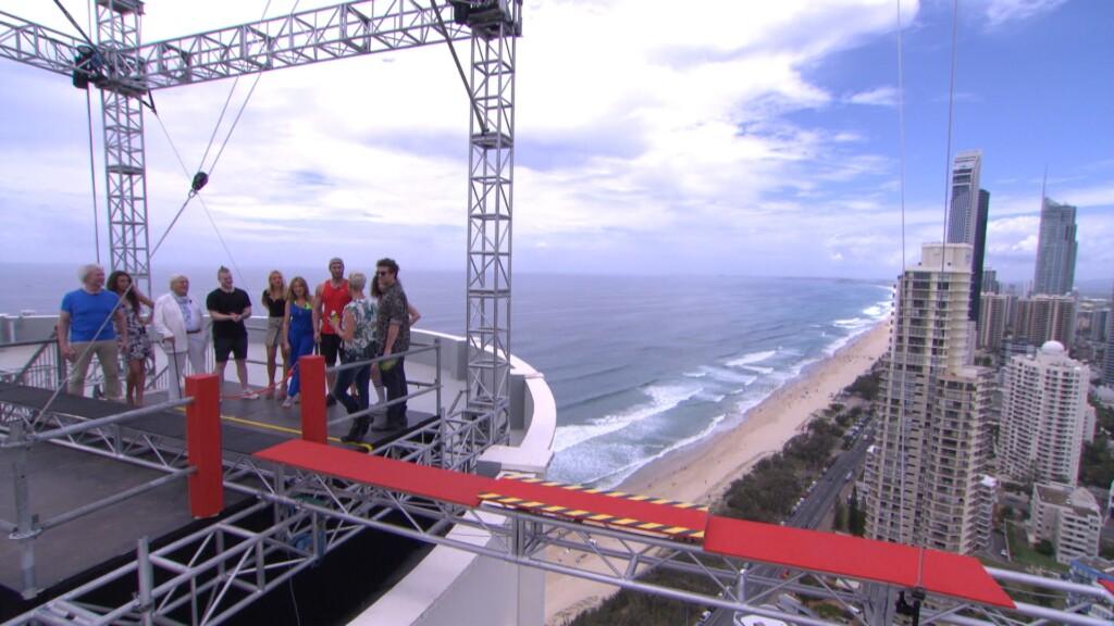 """Tag 1 - Dschungelprüfung """"Planke"""". Erstmals findet eine Dschungelprüfung außerhalb des Dschungels statt. Für die acht Kandidaten der ersten Gruppe geht es auf einen Wolkenkratzer in """"Surfers Paradise""""."""