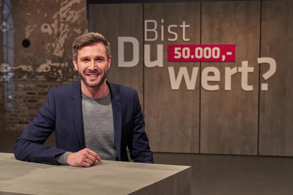 """""""Bist Du 50.000,- wert?"""": Moderator Jochen Schropp sitzt vor dem Sendungslogo."""