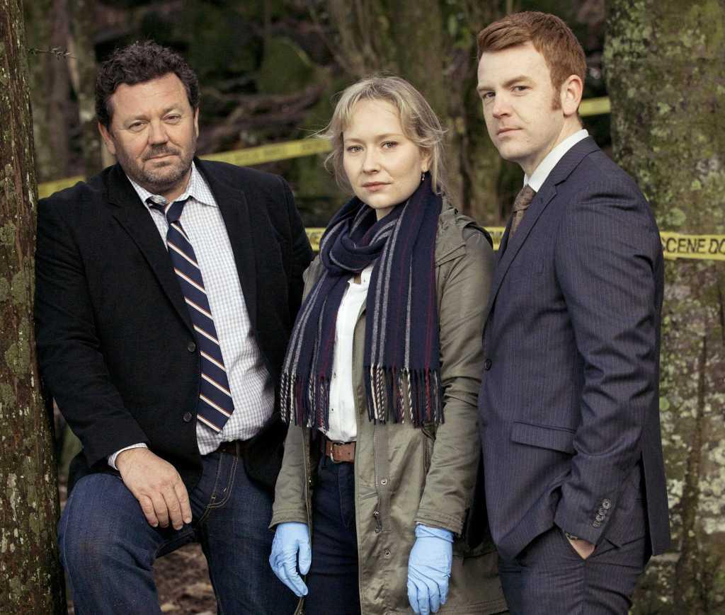 Detective Mike Shepherd (Neill Rea, li.) kommt mit dem Auftrag nach Brokenwood, den Tod des Farmers Nate Dunn aufzuklären. An seiner Seite ermitteln seine Mitarbeiterin Kristin Sims (Fern Sutherland) und der Polizist Breen (Nic Simpson).