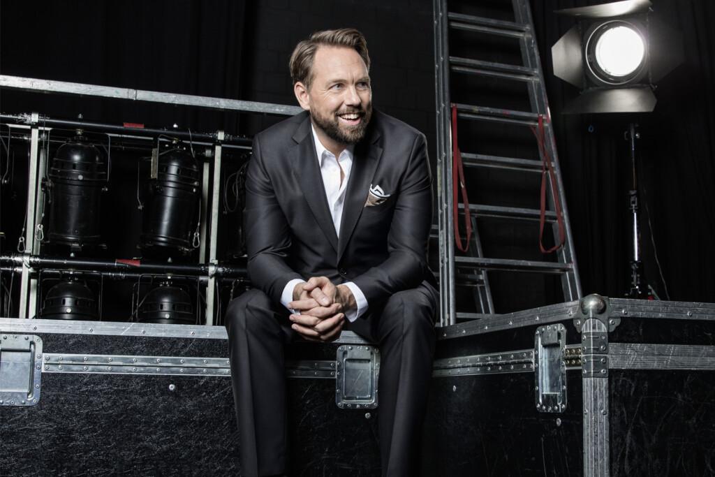 """""""Die versteckte Kamera 2016 - Prominent reingelegt!"""": Steven Gätjen backstage sitzend. Im Hintergrund Scheinwerfer und eine Leiter."""