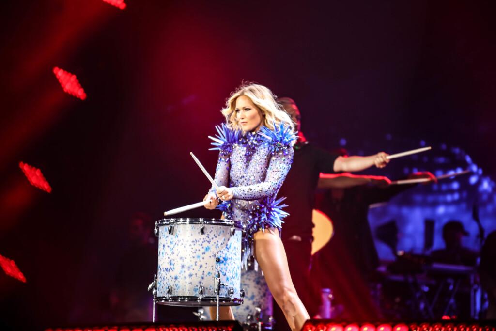 Helene Fischer steht auf der Bühne und trommelt. Sie trägt ein blaues, beinfreies Glitzerkostüm.