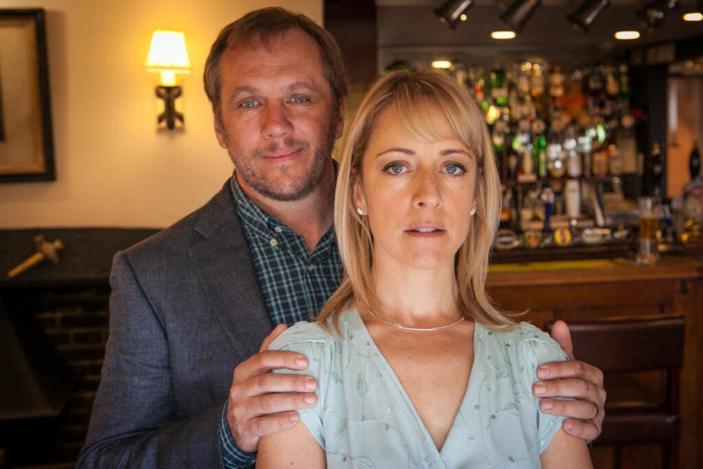 Tom Asher (Dean Andrews) legt glücklich den Arm um die Schultern seiner Frau Claire (Claudie Blakely), die weniger glücklich schaut.