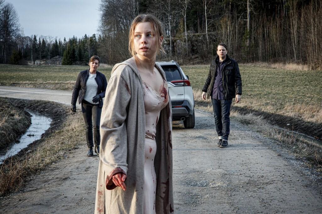 Ida Lind (Amanda Jansson, M.) konnte sich aus ihrer Gefangenschaft befreien und flüchten. Auf einem Feldweg stößt sie auf Alexandra Beijer (Jennie Silfverhjelm, l.) und Oskar Bergman (Måns Nathanaelsson, r.), die versuchen, die verstörte und panische Frau zu beruhigen.