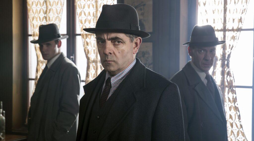 Kommissar Maigret (Rowan Atkinson) und seine Inspektoren Lapointe (Leo Staar, li.) und Janvier (Shain Dingwall, re.) nehmen das verlassene Bistro des Ermordeten unter die Lupe.