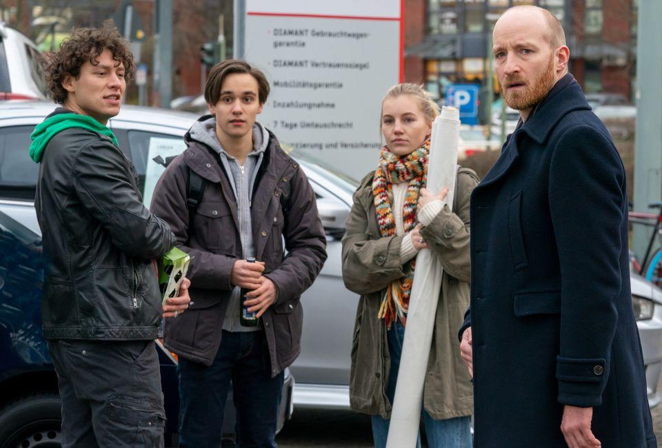 Der Klimaaktivist Finn Berger (Louie Betton, 2.v.l.) protestiert mit seinen Freunden Daniel (Malik Blumenthal, l.) und Elli (Louise Sophie Arnold) vor dem Autohaus von Jens Ehrenberg (Lukas Turtur, r.).