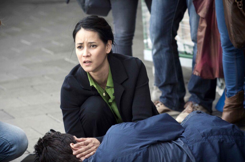 Ayumi Schröder (Luka Omoto) muss miterleben wie ihr Mann Ben (Markus Brandl) in ihren Armen stirbt.