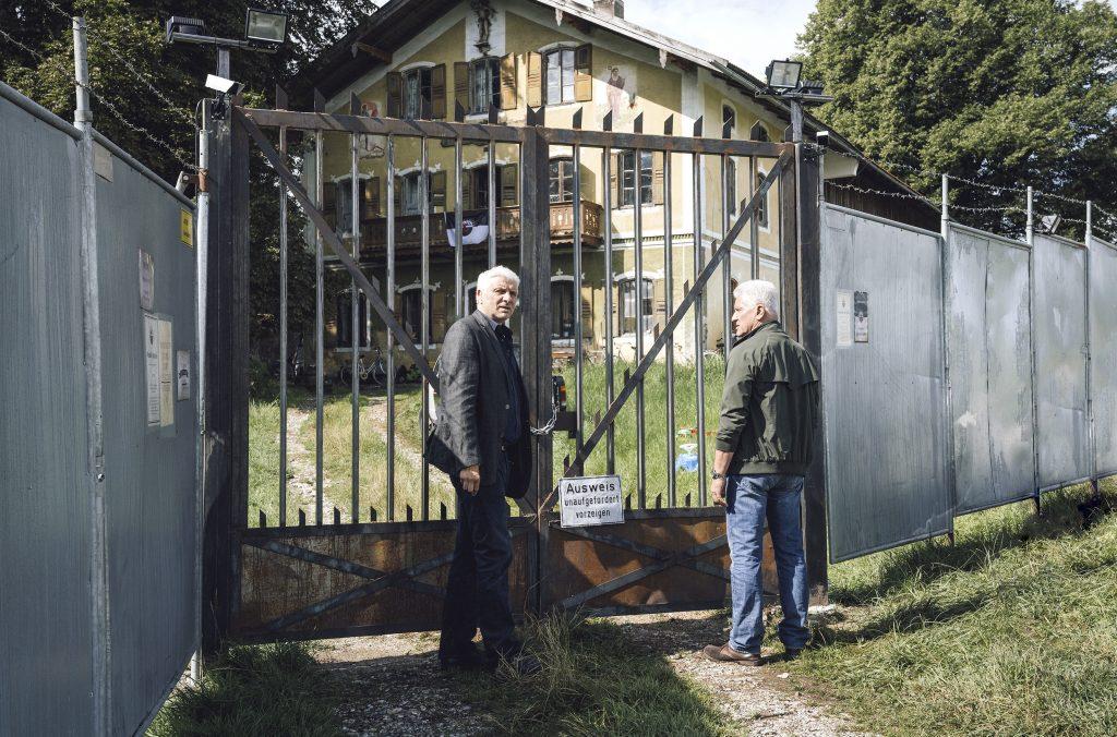 """Kriminalhauptkommissar Franz Leitmayr (Udo Wachtveitl, links) und Kriminalhauptkommissar Ivo Batic (Miroslav Nemec) stehen vor dem verschlossenen Eingangstor zum """"Freiland""""-Gelände."""