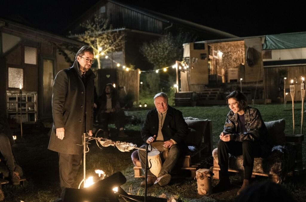 Abend auf dem Erlenhof: Prof. Karl-Friedrich Boerne (Jan Josef Liefers), Kommissar Frank Thiel (Axel Prahl) sitzen mit Inès Fournier (Maëlle Giovanetti, v.l.) am Lagerfeuer.