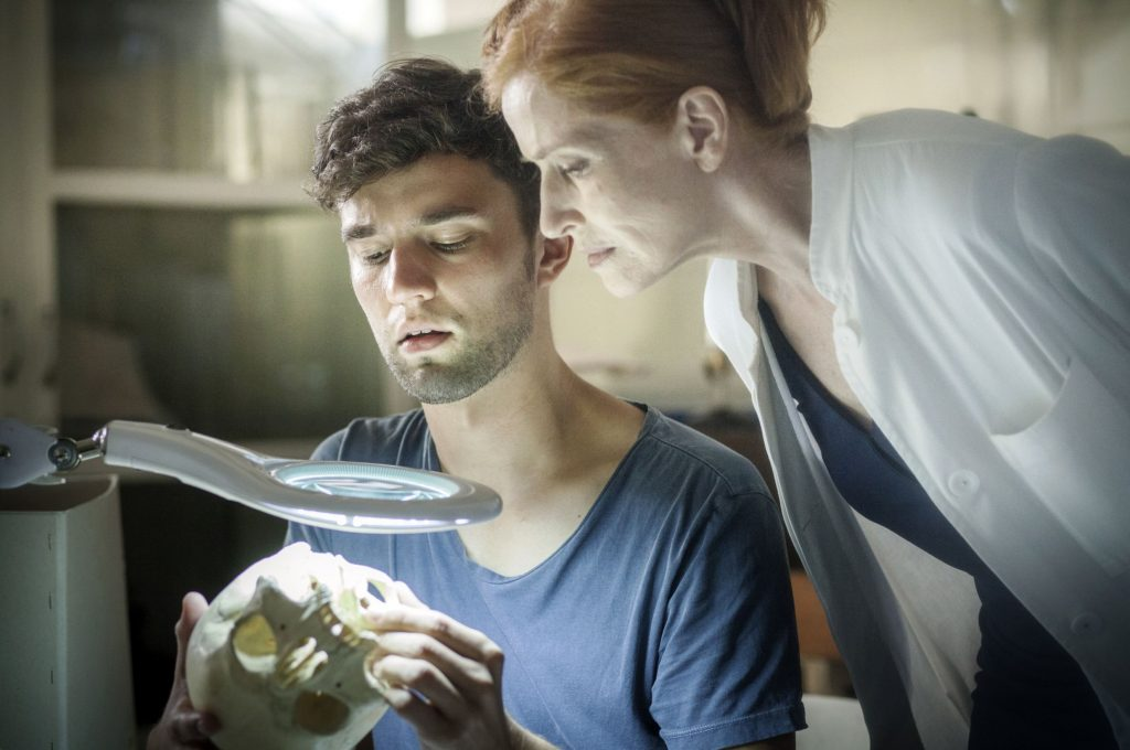 Von links: Der Doktorand Philip (Nils Strunk) zeigt Prof. Magdalena Mittlich (Sibylle Canonica) einen Schädel.