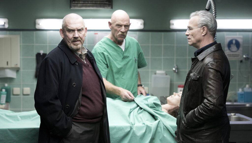 Gerichtsmediziner Dr. Joseph Roth (Joe Bausch, M) liefert den Kommissaren Max Ballauf (Klaus J. Behrendt, r) und Freddy Schenk (Dietmar Bär) die genauen Tatumstände.