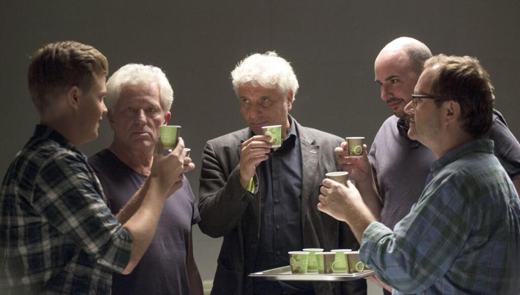 Das Team stößt mit Espresso in Pappbechern auf das 25-jährige Dienstjubiläum von Batic und Leitmayr an.