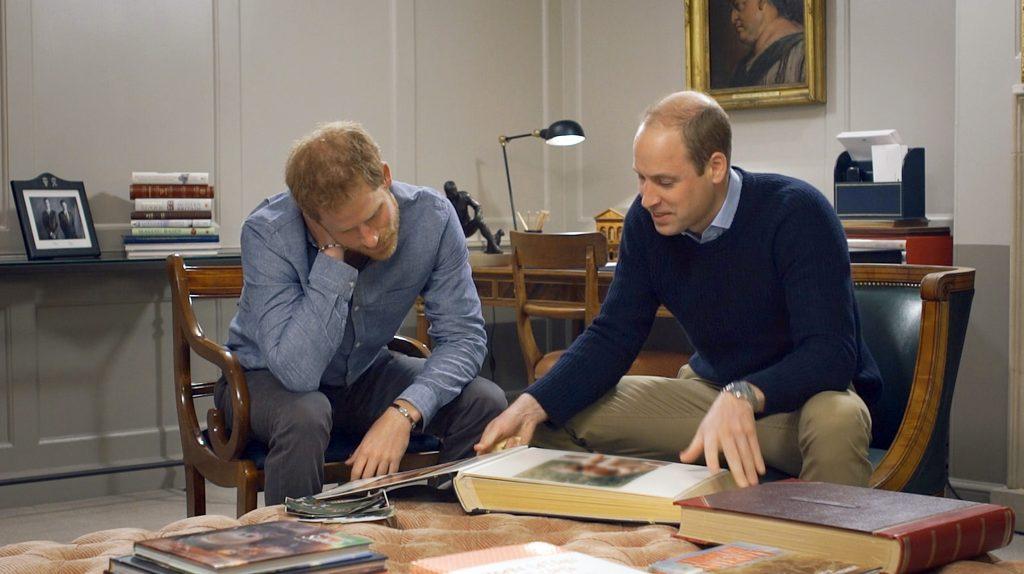 Prinz Harry und Prinz William schauen sich ein Fotoalbum an.